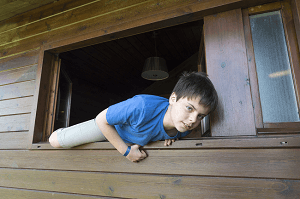 Child climbing out of a Window